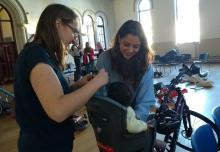 A mum is helped to put her toddler in a child bike seat